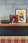 Vintage radios, and a Jimi Hendrix album and art print lean on a shelf.