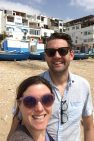 Lindsey and her husband stand on the beach taking a selfie. There are docked boats and building in the background, all in white and blue.