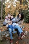 Mira and her husband cuddle their kids on a bench in a park. It's fall and there are yellow leaves on the trees and ground.